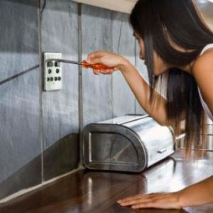 woman repairing outlet with screwdriver